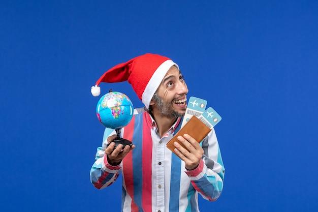 Widok z przodu regularny mężczyzna z biletami i kulą ziemską na niebieskiej ścianie wakacje nowy rok kolor