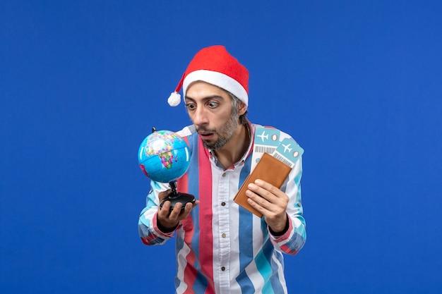 Widok z przodu regularny mężczyzna z biletami i kulą ziemską na niebieskim biurku emocje wakacje nowy rok