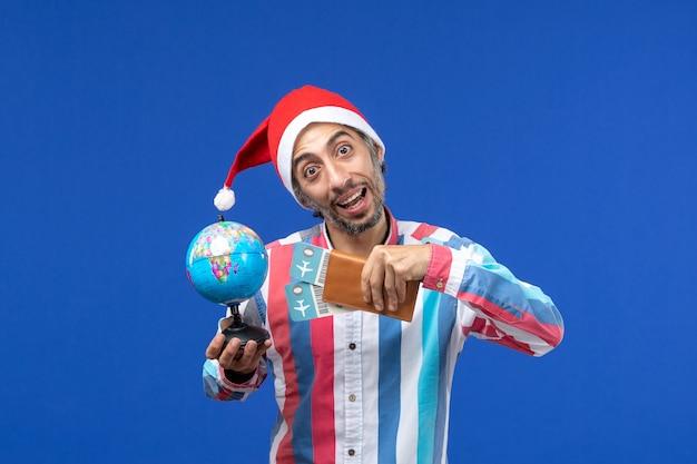 Widok z przodu regularny mężczyzna z biletami i kulą ziemską na niebieskim kolorze ściany wakacje nowy rok