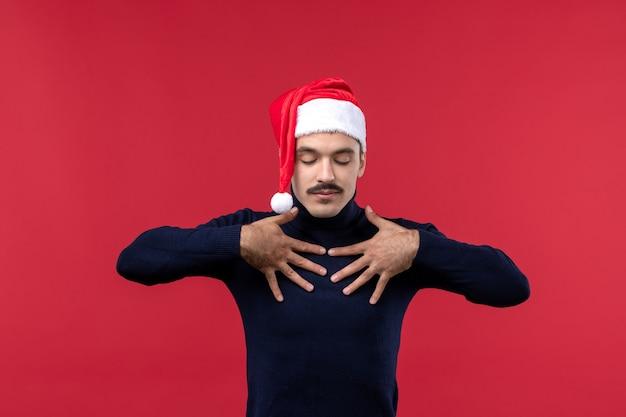 Widok z przodu regularny mężczyzna z czerwoną czapką świąteczną na czerwonym tle
