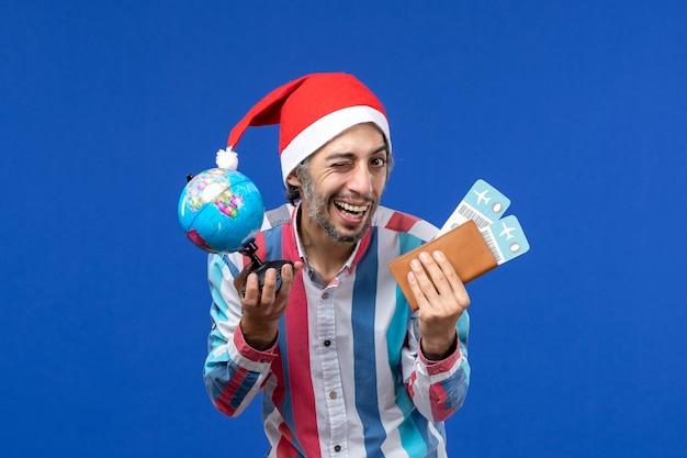 Widok z przodu regularny mężczyzna z kulą ziemską i biletami na niebieskiej ścianie emocje wakacje nowy rok