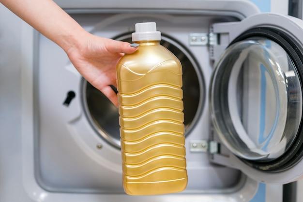 Widok z przodu ręka trzyma butelkę detergentu