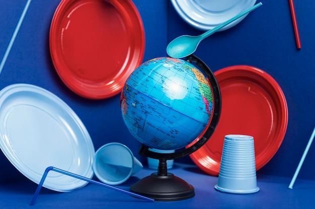 Widok z przodu rękawicy ziemskiej z plastikowymi talerzami i filiżankami