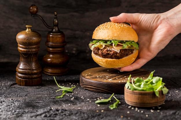 Widok z przodu ręki trzymającej burgera wołowego z sałatką i boczkiem