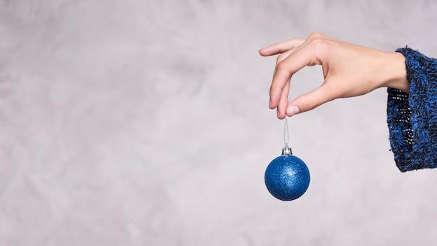 Widok z przodu ręki trzymającej piłkę bożego narodzenia