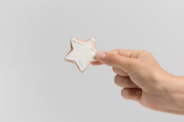 Widok z przodu ręki trzymającej plik cookie gwiazdy bożego narodzenia