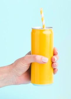 Widok z przodu ręki trzymającej puszkę napoju ze słomką