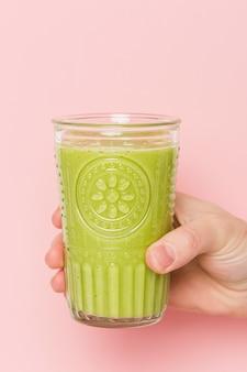 Widok z przodu ręki trzymającej szklankę z smoothie