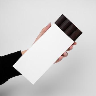Widok z przodu ręki trzymającej tabletkę czekolady z opakowaniem
