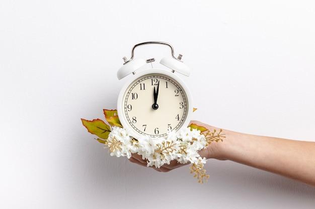Widok z przodu ręki trzymającej zegar z kwiatami
