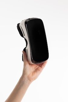 Widok z przodu ręki trzymającej zestaw słuchawkowy wirtualnej rzeczywistości