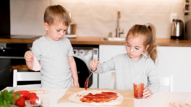Widok z przodu rodzeństwa gotuje w domu