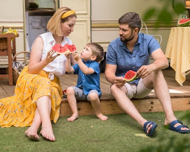 Widok z przodu rodziny jedzących razem arbuza obok przyczepy kempingowej