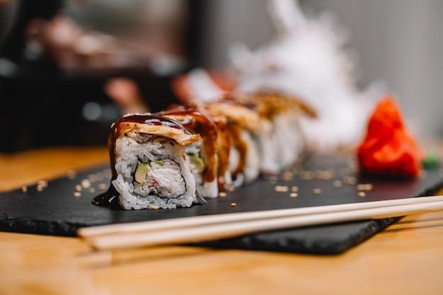 Widok z przodu rolki sushi z węgorzem i sosem na stojaku
