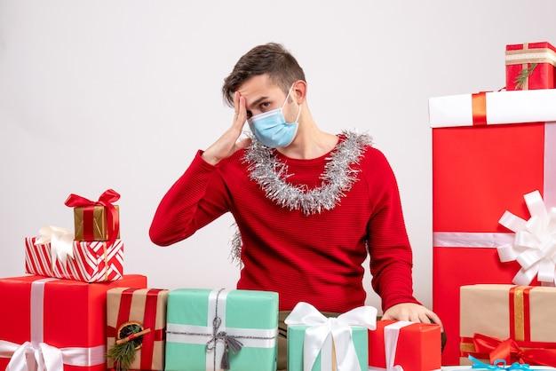 Widok z przodu rozczarowany młody człowiek z maską siedzi wokół prezentów bożonarodzeniowych