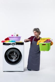 Widok z przodu roześmiany mężczyzna gospodyni klęczący w pobliżu pralki trzymający kosz na pranie na białym tle