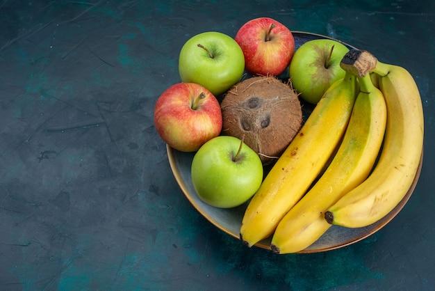 Widok z przodu różne kompozycje owoców kokosowe jabłka i banany na ciemnoniebieskim biurku owoce świeże łagodne egzotyczne tropikalne