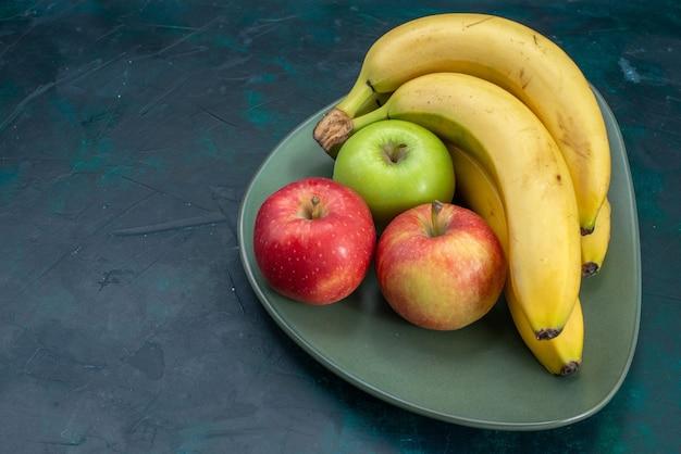 Widok z przodu różne kompozycje owocowe jabłka i banany na ciemnoniebieskim biurku owoce świeże łagodne egzotyczne tropikalne