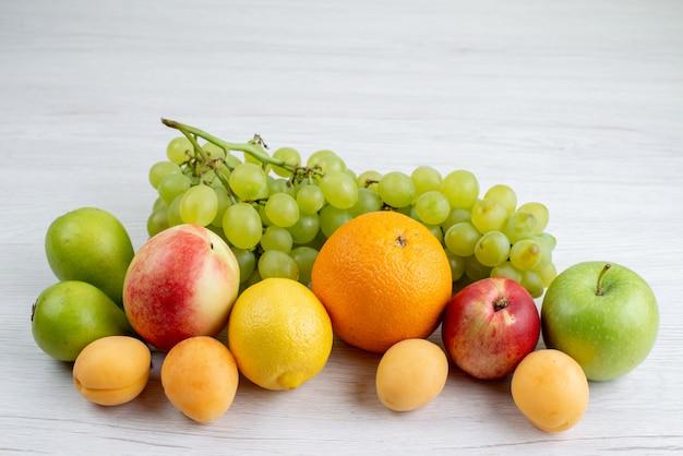 Widok z przodu różne owoce łagodne i świeże owoce, takie jak morele, winogrona, jabłka na białym biurku, kompozycja owoców, kolor, witamina