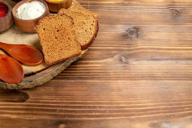 Widok z przodu różne przyprawy z bochenkami chleba na brązowej przestrzeni