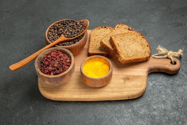 Widok z przodu różne przyprawy z ciemnymi bochenkami chleba na ciemnoszarym tle bułka chlebowa pikantna gorąca przyprawa