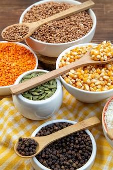 Widok z przodu różne surowe kasze ryż kukurydziany soczewica i gryka na talerzach na brązowym tle roślina jedzenie świeża zupa kolory nasion