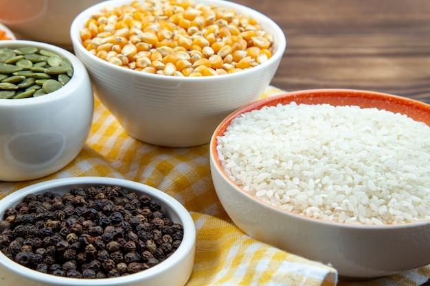 Widok z przodu różne surowe kasze ryż kukurydziany soczewica i gryka na talerzach na brązowym tle roślina kolor jedzenie zupa nasiona