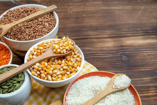 Widok z przodu różne surowe kasze ryż kukurydziany soczewica i gryka na talerzach na brązowym tle roślina świeża zupa kolor nasion