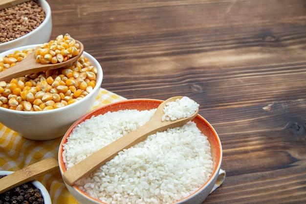 Widok z przodu różne surowe kasze ryż kukurydziany soczewica i kasza gryczana na talerzach na brązowym tle roślina jedzenie świeża zupa kolor nasion
