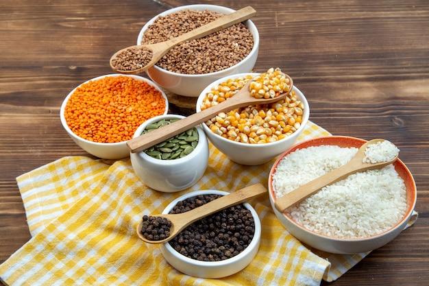 Widok z przodu różne surowe kasze ryż kukurydziany soczewica i kasza gryczana na talerzach na brązowym tle roślina kolor jedzenie świeże nasiona