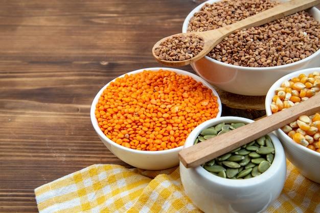 Widok z przodu różne surowe kasze ryż kukurydziany soczewica i kasza gryczana na talerzach na brązowym tle żywność świeża zupa kolor nasion