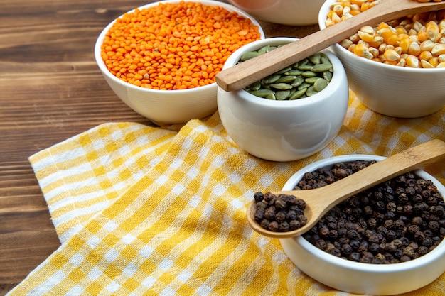 Widok z przodu różne surowe kasze ryż kukurydziany soczewica i kasza gryczana w talerzach na brązowym tle roślina kolor jedzenie świeże zupy nasiona drewno