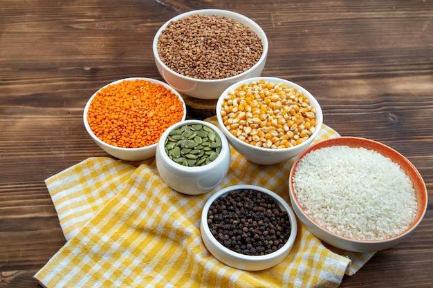 Widok z przodu różne surowe składniki ryż kukurydza soczewica i gryka wewnątrz talerza na brązowym drewnianym tle jedzenie zupa świeży kolor roślin
