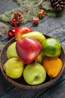 Widok z przodu różne świeże owoce wewnątrz brązowego talerza na ciemnoniebieskim biurku kompozycja kolorystyczna owoców świeża dojrzała
