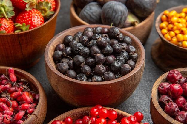 Widok z przodu różne świeże owoce wewnątrz talerzy na ciemnym tle owoce kolorowe zdjęcie wiele łagodnych soków