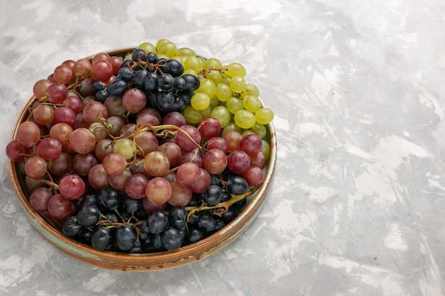 Widok z przodu różne winogrona soczyste łagodne kwaśne owoce na jasnym białym biurku owoce świeży łagodny sok wino