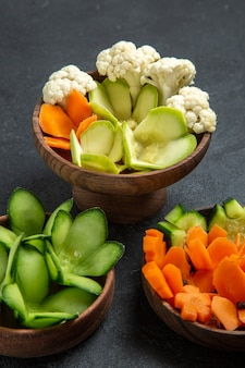 Widok z przodu różne zaprojektowane warzywa w doniczkach na ciemnoszarej przestrzeni