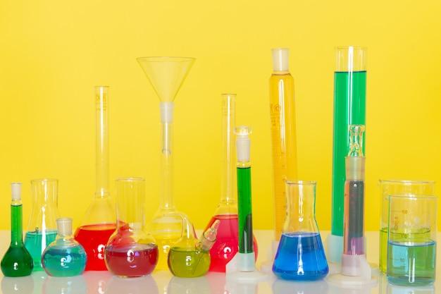 Widok z przodu różnych kolorowych roztworów wewnątrz kolb na stole