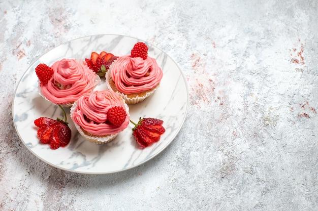 Widok z przodu różowe ciasta truskawkowe ze świeżymi czerwonymi truskawkami na białej przestrzeni
