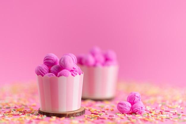 Widok z przodu różowy, ciasteczka pyszne i pyszne wraz z kolorowymi cukierkami na różowym, cukierkowym cukierku herbatnikowym