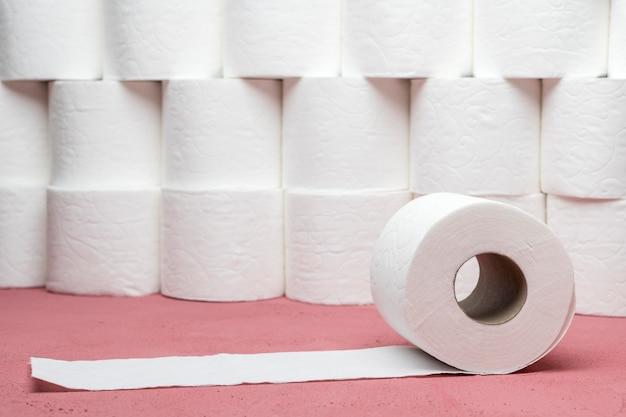 Widok z przodu rzędu ułożonych rolek papieru toaletowego z jednym rozwiniętym