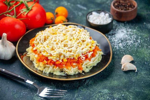 Widok z przodu sałatka z mimozy wewnątrz talerza z przyprawami i pomidorami na ciemnoniebieskiej powierzchni kuchnia zdjęcie kuchnia urodziny posiłek kuchnia kolor żywności