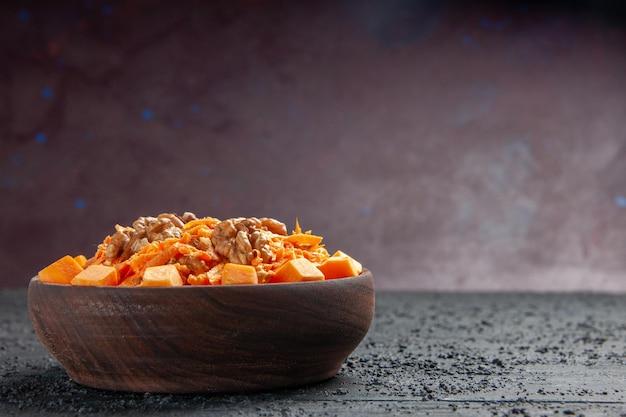 Widok z przodu sałatka ze świeżej marchewki tarta sałatka z orzechami włoskimi i czosnkiem na ciemnym biurku sałatka dietetyczna kolor orzechów zdrowie