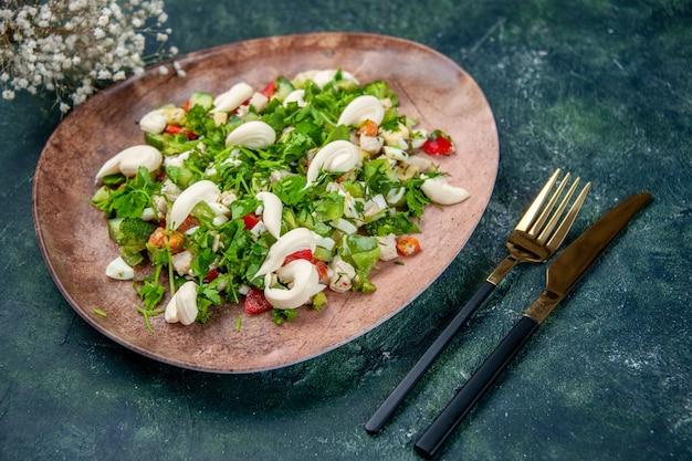 Widok z przodu sałatka ze świeżych warzyw wewnątrz eleganckiego talerza ze sztućcami na ciemnoniebieskim tle