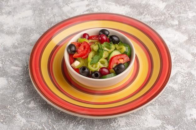 Widok z przodu sałatka ze świeżych warzyw z pokrojonymi ogórkami, pomidorami, oliwą i białym serem wewnątrz talerza na szarej powierzchni jedzenie warzywne sałatka posiłek przekąska zdjęcie
