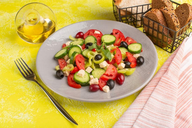 Widok z przodu sałatka ze świeżych warzyw z pokrojonymi ogórkami pomidory oliwka wewnątrz talerza z olejem i chlebem na żółtej powierzchni jedzenie warzywne sałatka posiłek kolor przekąska
