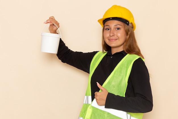 Widok z przodu samica konstruktora w żółtej koszuli kasku, trzymając farbę z uśmiechem na białej ścianie kobieta architekta konstruktora