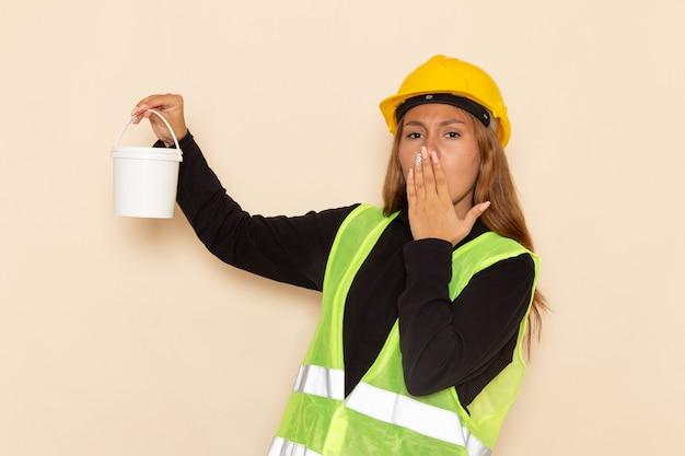 Widok z przodu samica konstruktora w żółtym kasku czarnej koszuli trzyma farbę ziewanie na białym biurku kobieta architekta konstruktora