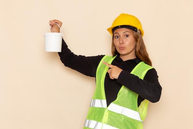 Widok z przodu samica konstruktora w żółtym kasku czarnej koszuli trzyma puszkę farby na białej ścianie kobieta architekta konstruktora