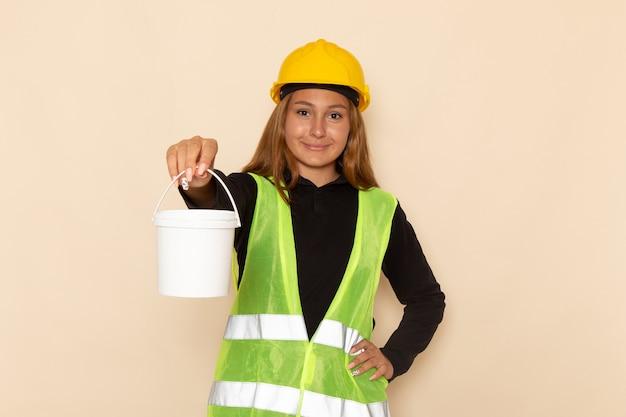 Widok z przodu samica konstruktora w żółtym kasku trzyma farbę i uśmiecha się na białej ścianie kobieta architekt budowy konstruktora